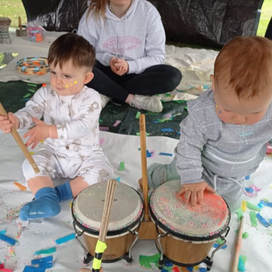 Babies playing drums in outdoors creative play session
