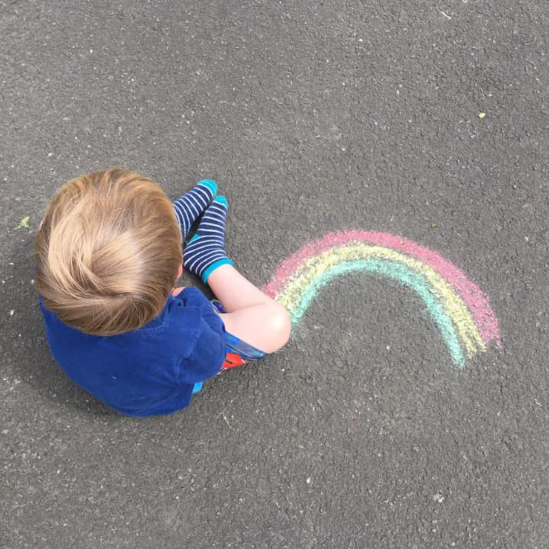 Young boy sitting next to chalk rainbow on the pavement